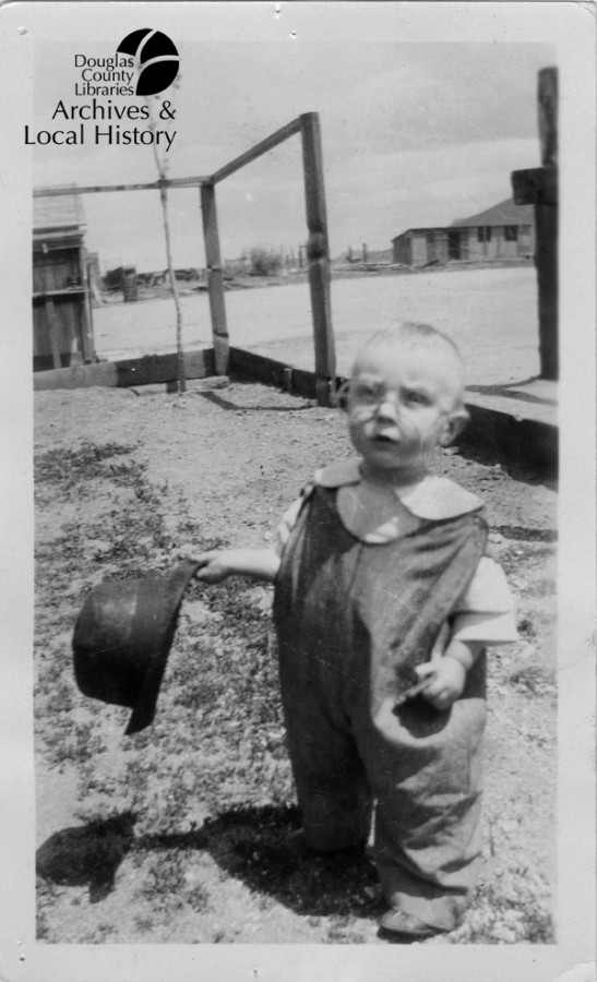 Image shows a baby about one year old. He is in overalls, wearing glasses and holding a man's top hat. He is in a yard and it is the 1920s or 1930s.