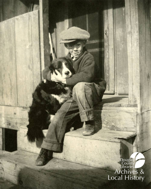 Image shows a young boy hugging a dog while sitting on wooden porch steps. He is wearing clothing from the 1920s or 1930s and the dog is a border collie mix.