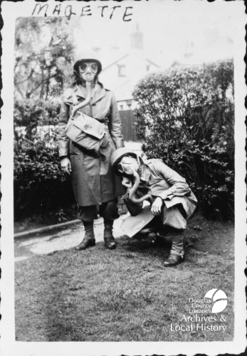 Image shows two nurses in gas masks and World War II combat gear. One woman is kneeling and one is standing.