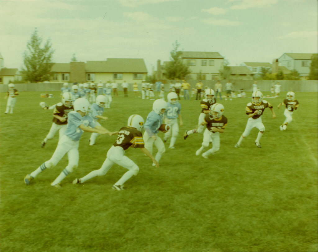 Color image shows children playing a youth football game. The teams are the Dolphins in blue and the Titans in black. A Dolphins player has the football.