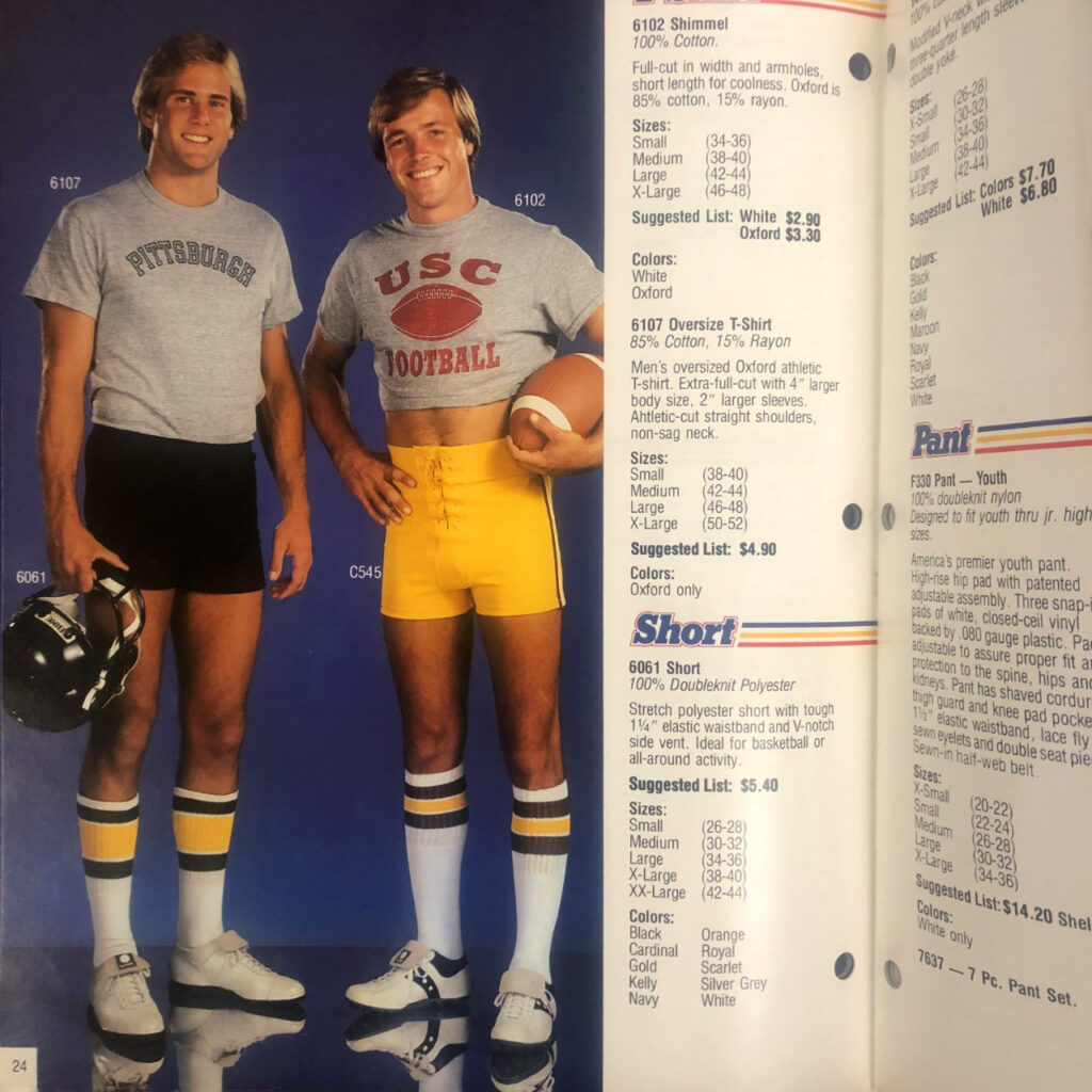 Color image shows a page from a 1980 sports uniform catalog. Two men are modeling football uniforms, wearing short shorts and one is wearing a crop top.