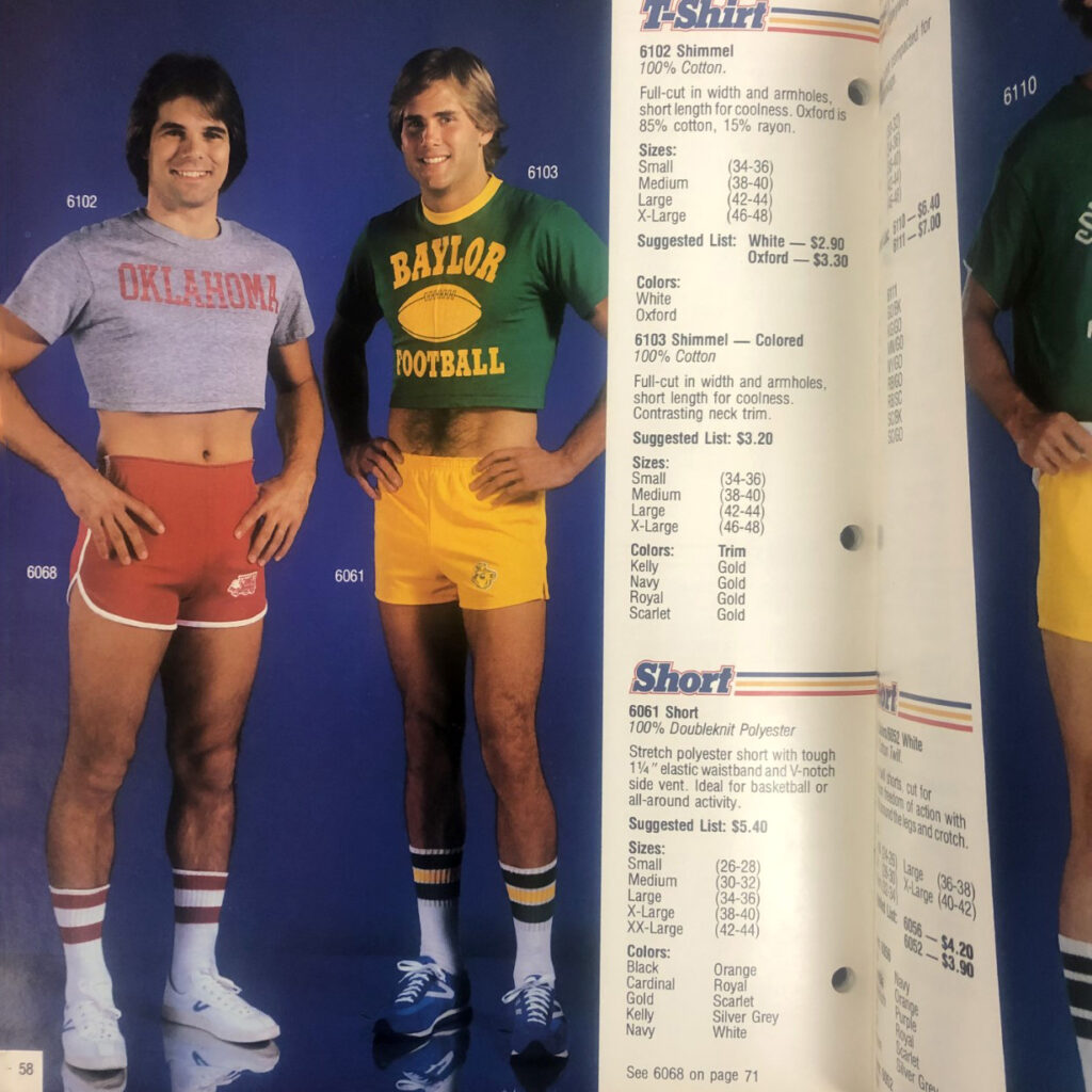 Color image shows a page from a 1980 sports uniform catalog. Two men are modeling football outfits, with crop tops, short shorts, and long striped socks.